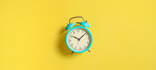 Turquoise vintage alarm clock on yellow background. Top view. Flat lay