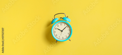 Photo Turquoise vintage alarm clock on yellow background