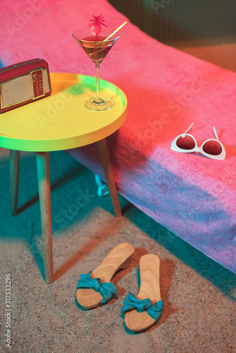 Vintage 1950s ladies shoes on beach next to sunbed and yellow table with cocktail beverage on it Canvas Print