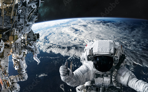 Obraz Astronauts and the ISS in orbit of the planet Earth. Solar system. Science fiction. Elements of this image furnished by NASA - fototapety do salonu