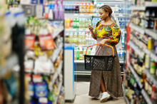 Happy African Woman In Traditional Clothes And Veil Looking Product At Grocery Store, Shopping In Supermarket.  Afro Black Women With Mobile Phone.