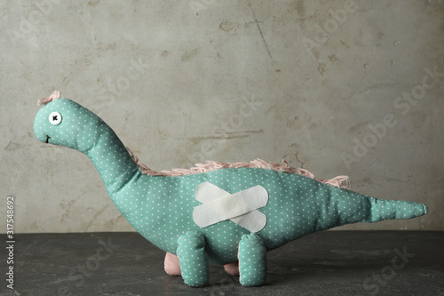 Fototapeta Toy dinosaur with sticking plasters on grey stone table obraz