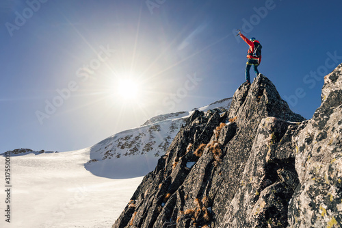 Climber or alpinist at the top of a mountain Canvas Print