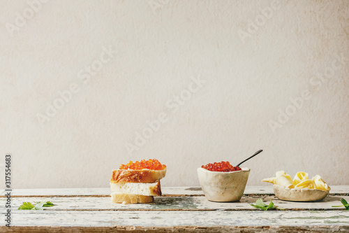 Red salmon caviar in ceramic bowl and on wheat bread, served with butter on old wooden table Wallpaper Mural