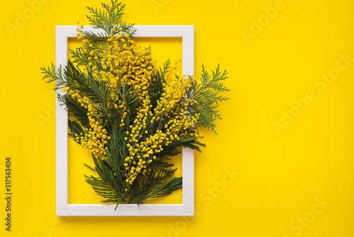 Fotomural Mimosa flowers and green branches  on yellow pattern texture of crumpled paper with white photo frame, yellow background