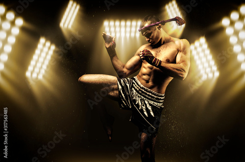 Kickboxer in the ring surrounded by searchlights stretches before the fight Canvas Print