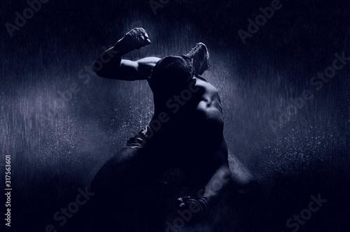 Fotografia Thai boxer in the rain and under a blue spotlight