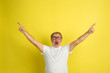 Pointing at sides. Caucasian man portrait isolated on yellow studio background. Beautiful male model in white shirt posing. Concept of human emotions, facial expression, sales, ad. Copyspace.