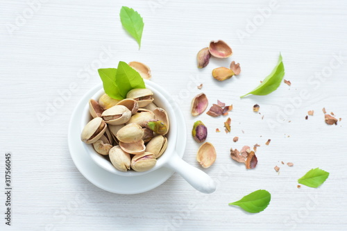 Photo Pistachios on the white wooden background, accompanied by green leaf