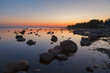 canvas print picture - Colorful sunset with clear sky over rocky shore of Baltic sea.