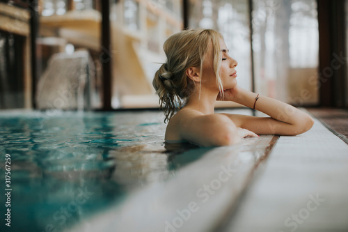 Obraz Young woman relaxing in spa swimming pool - fototapety do salonu