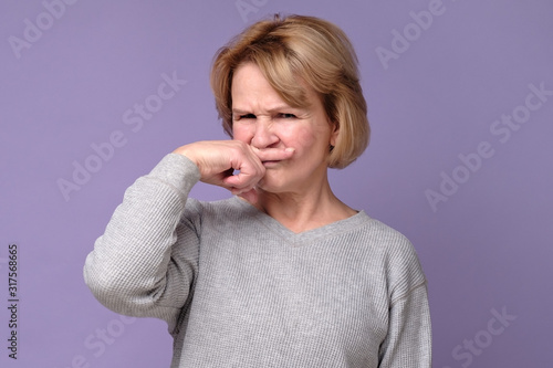 Handsome expressive grandmother coering nose from hodor and bad smell from kitchen Canvas Print