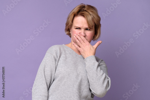 Handsome expressive grandmother coering nose from hodor and bad smell from kitchen Wallpaper Mural