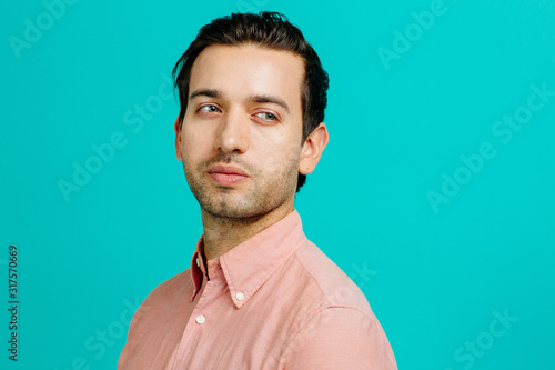 Canvastavla Portrait of a young adult man thinking,  isolated on blue studio background