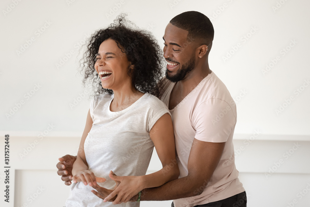 Fototapeta African couple spending weekend fooling around having fun at home