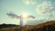 Rear View Of Beautiful Girl Angel On A Hill Raised Its Wings Up And Enjoys The Sun And Sunbeams