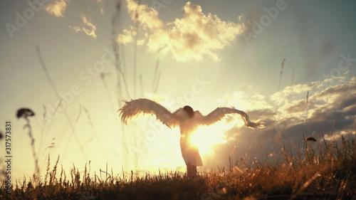 Fototapeta White angel and sun. Brunette girl in a white dress raises angel wings up, looks at the sun obraz