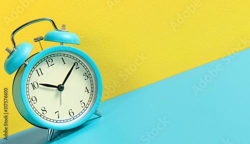 Alarm clock on turquoise yellow background. Canvas Print