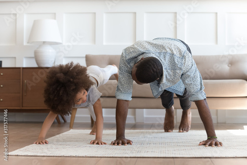 Foto African father and little daughter do push-up exercise indoors