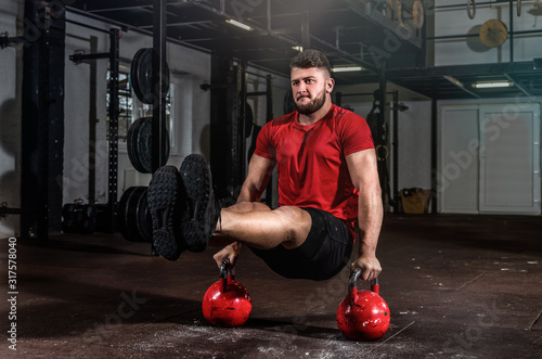 Fotografie, Tablou Young strong fit sweaty muscular man doing handstand on the two old heavy kettle