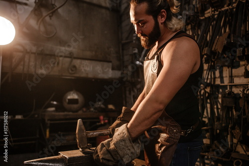 Portrait of a brutal muscular blacksmith standing in a dark workshop forging iro Wallpaper Mural