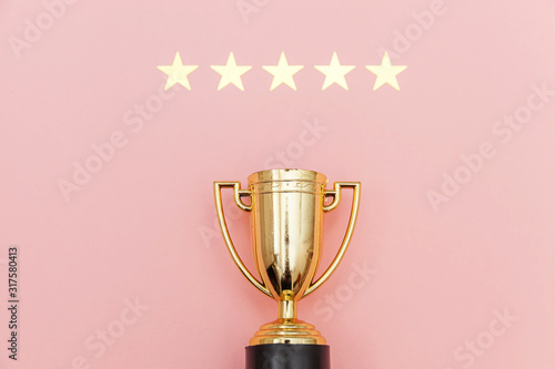 Fototapeta Simply flat lay design winner or champion gold trophy cup and 5 stars rating isolated on pink pastel background. Victory first place of competition. Winning or success concept. Top view copy space. obraz