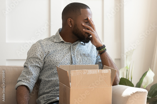 Fotografía African guy feels stressed saw that goods in parcel damaged