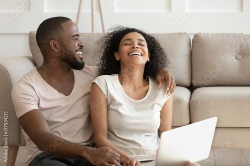 Fotografija Cheerful african couple having fun using online websites at home
