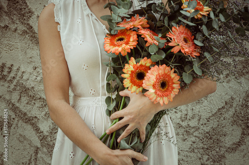Photo Bouquet of gerberas in the arms of a woman.