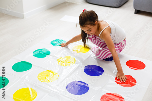Obraz na plátně little girl plays twister at home