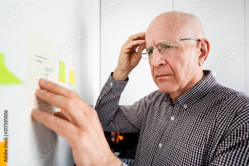 Elderly man with dementia looking at notes Wallpaper Mural