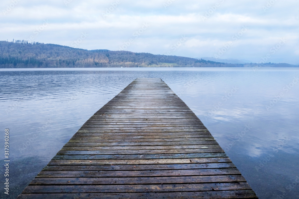 Fototapeta A long wooden jetty on a lake, jutting sraight out over a clear calm blue lake