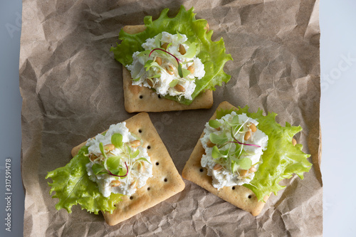 Fototapeta toast for Breakfast of tender, juicy sprouted beet sprouts with soft cheese, salad and wheat sprouts on a sheet of paper on a white background