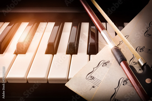 Bow with sheet music on piano keys front