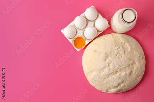 Fototapeta  Raw dough and ingredients for pastries on pink background, flat lay