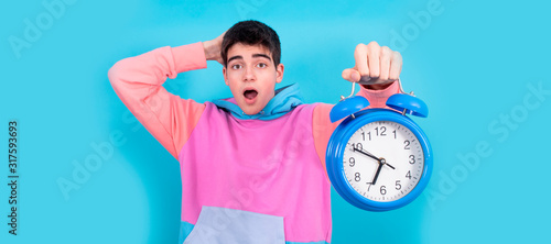 amazed young teenage man with alarm clock or clock isolated on background Canvas Print