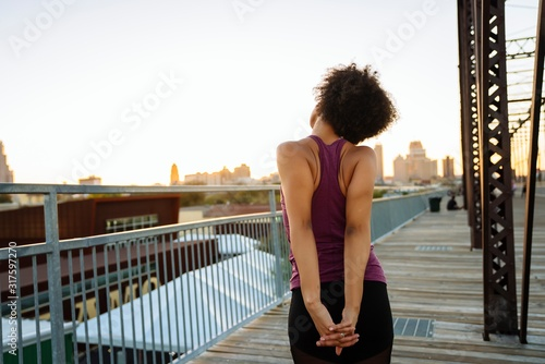 Woman in fitness attire stretching arms on pedestrian bridge in city at sunset Canvas Print
