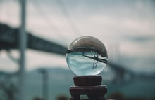 Closeup Shot Of A Crystal Ball With The Reverse Reflection Of A Bridge