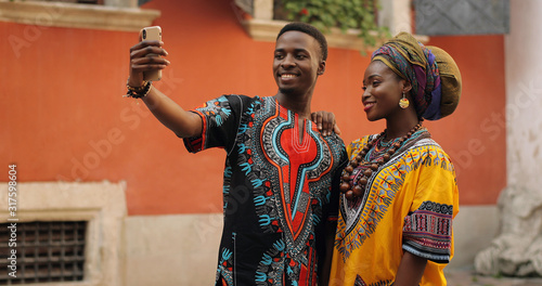 Fotografie, Obraz African young stylish and attractive couple in traditional outfits standing together outside and posing to the smartphone camera while taking selfie photo