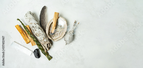 Smudge kit for spiritual practices with natural elements: Palo Santo sticks, dried white sage, Guinea Fowl feather, crystals, sea pearl shell Abalone on a light background Wallpaper Mural
