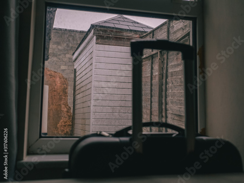 Cuadros en Lienzo  View on a small ugly backyard in a budget accommodation, Travel case by the window out of focus