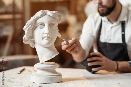 Foto Skillful sculptor makes professional restauration of gypsum sculpture of woman's head at the creative workshop