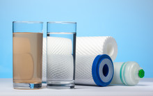 Glasses Of Dirty And Clear Water And Filter Cartridges