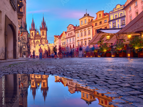 Fotografía St Mary Tyn Church in Prague with reflection in a pool of water after Summer rain with tourists walking by towards Old Town Square