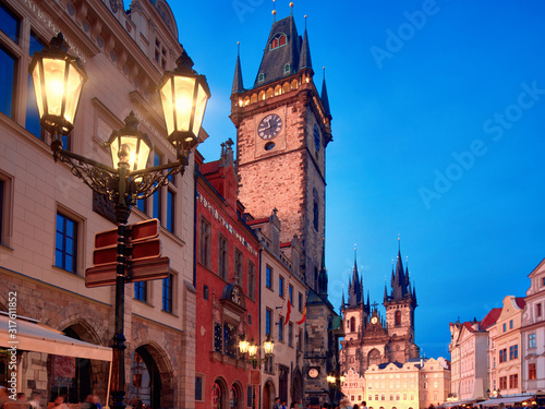 Prague, Old City Hall on the Town Square early evening with street lights. Historic architecture of houses and church of St. Mary before Tyn illuminated with sunset. Beautiful Prague on sunset.