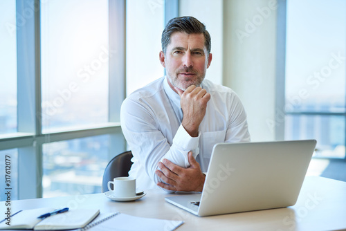 Canvastavla Handsome mature businessman with laptop in office looking serious
