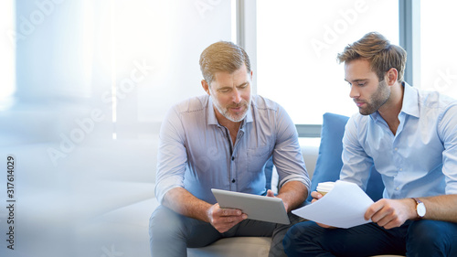 Fototapeta Mature businessman talking with younger colleague on couch obraz