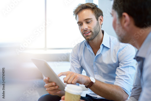 Fotografiet Young businessman presenting ideas with digital tablet