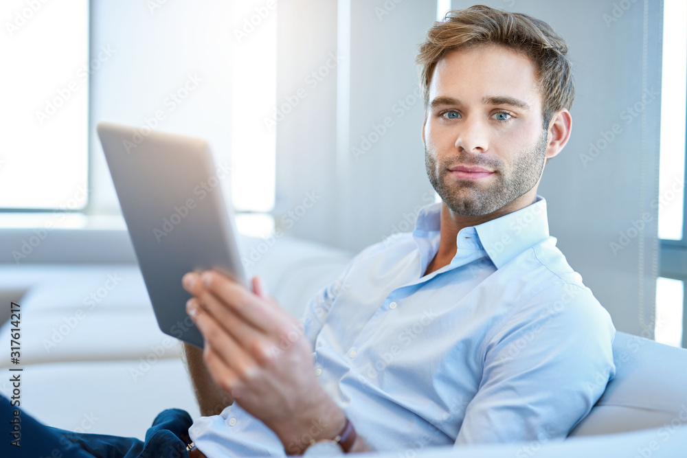 Fototapeta Handsome young businessman looking at camera with digital tablet