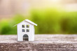 Miniature white toy model house in wooden background near green backdrop
